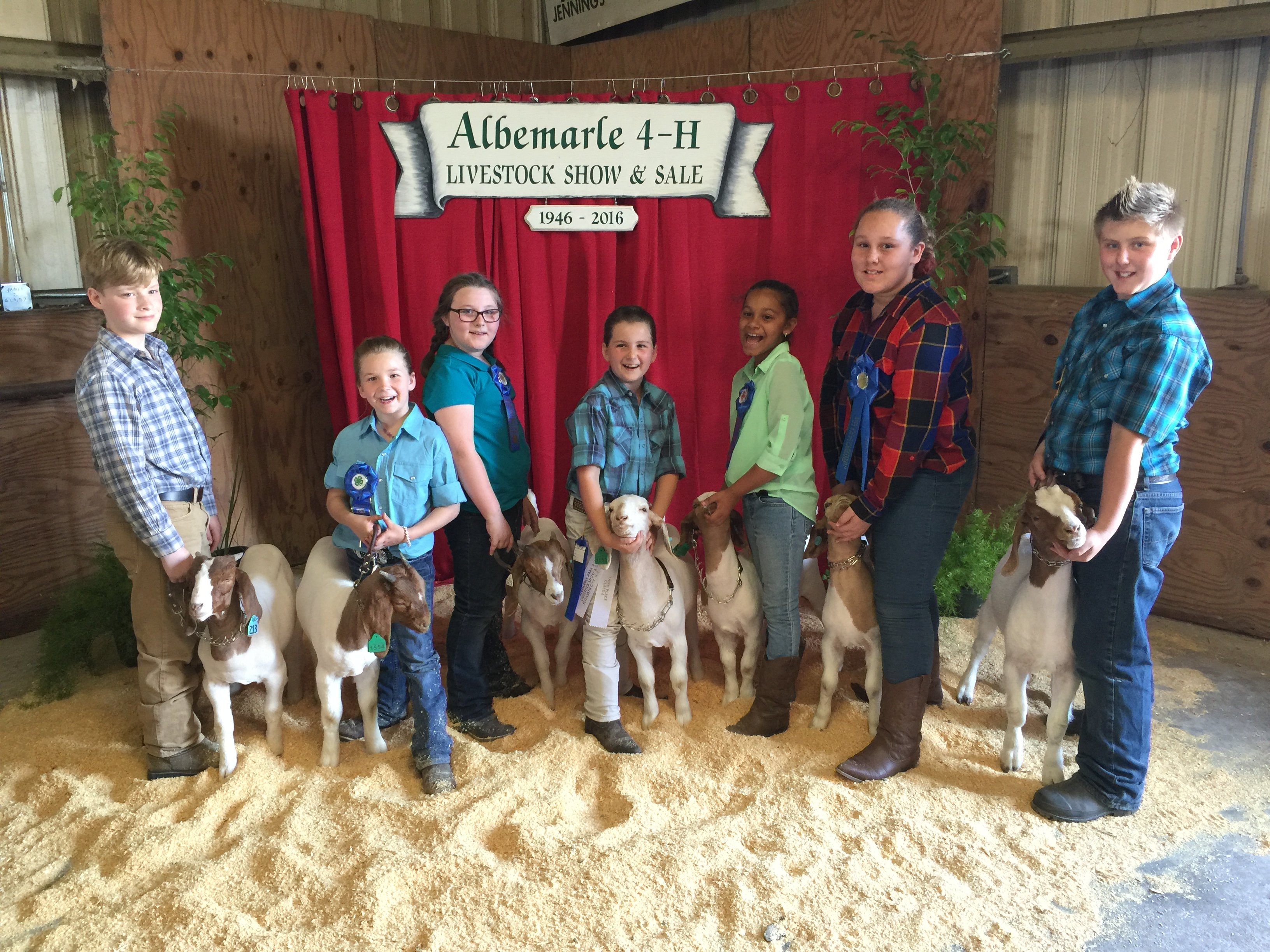 Children standing in front of 4-H sign with goats