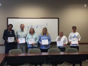 volunteers holding their certificates