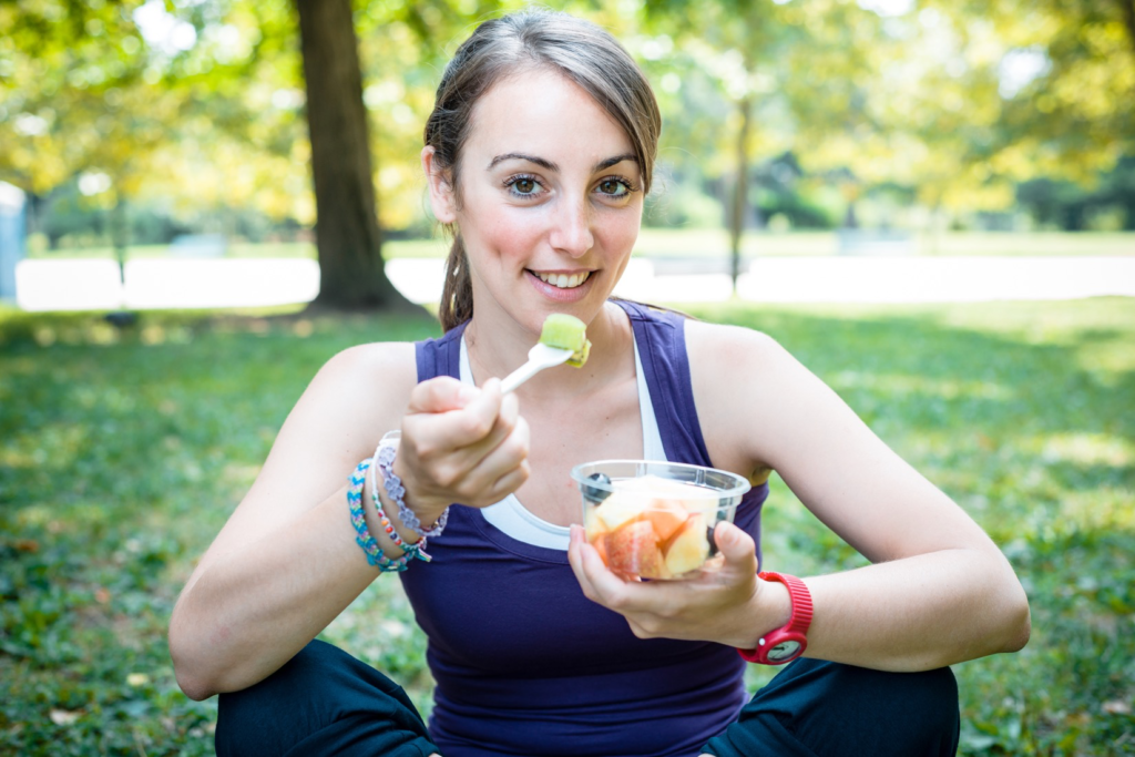 A girl eating a cup of fruit