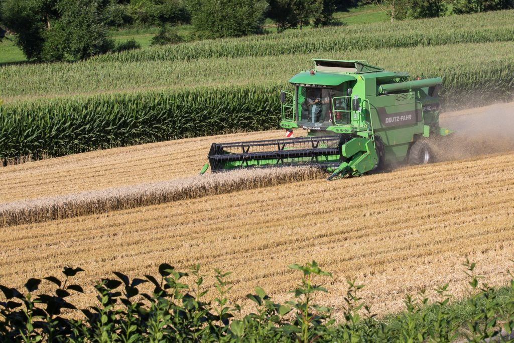 tractor picking wheat in field