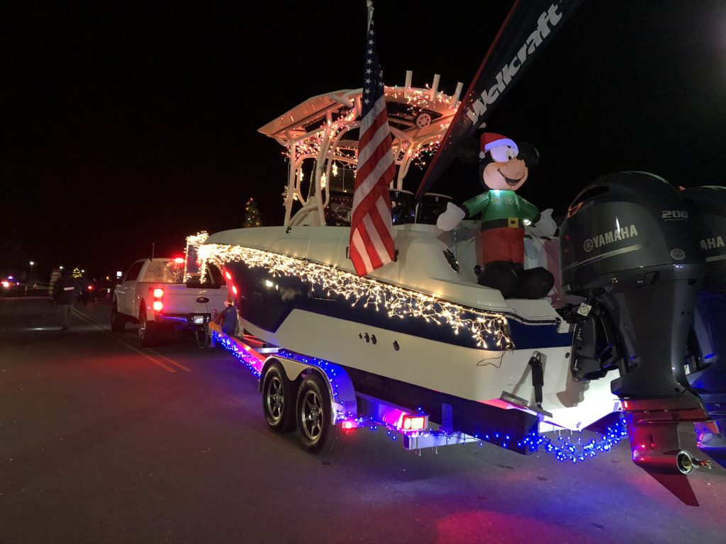 Boat float pulled by truck in parade with lights , flag and mickey mouse