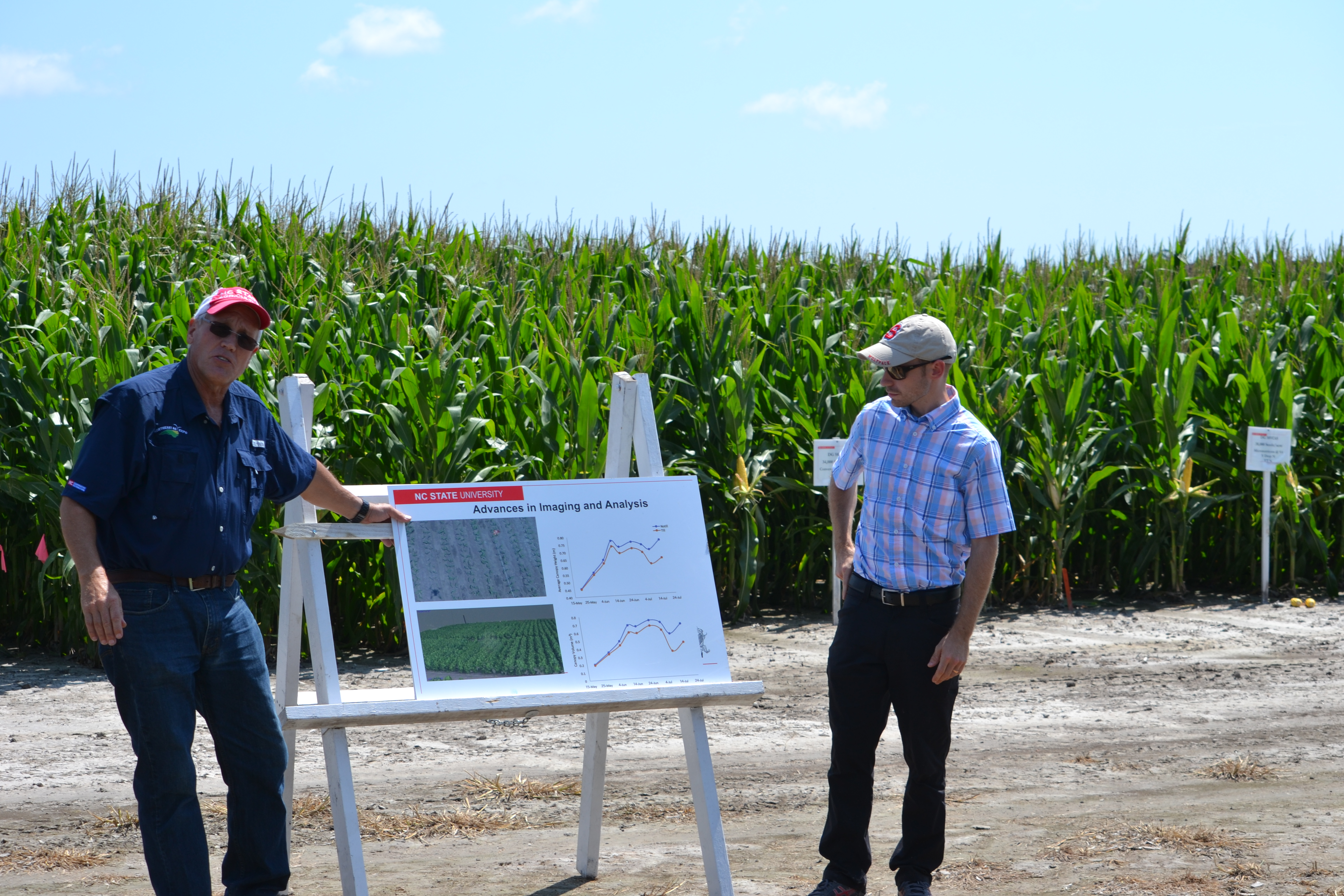 2 people looking at farm info with corn in background