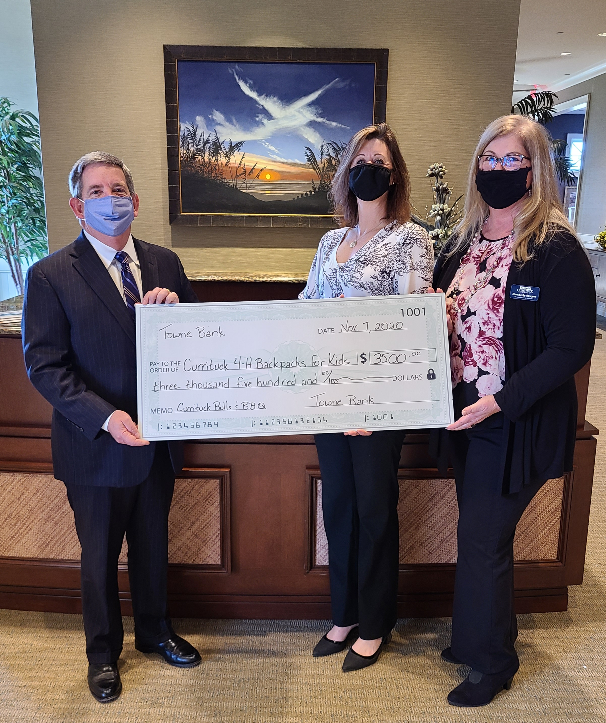 Taylor Sugg, President of TowneBank,, Cameron Lowe, Director of Currituck NC Extension and Kemberly Sawyer, Promo & Events Coordinator of Currituck Travel & Tourism holidng large donation check