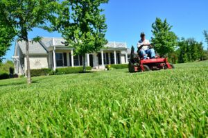 man mowing grass on riding lawnmower with house in background